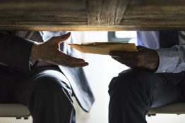 Business people sending documents under the table